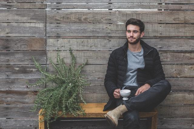 muž sedí na dřevěné lavičce