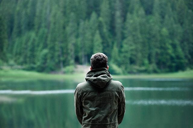 muž stojí v bundě před jezerem